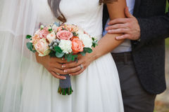 Wedding bouquet in bride hands standing next to groom Royalty Free Stock Photos