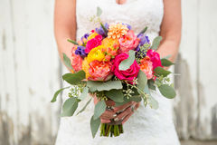 Wedding bouquet. Bride holding wedding bouquet outside in front of barn Stock Photo