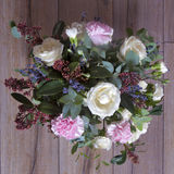 The Wedding bouquet of a bride from a rose, a pink carnation, eucalyptus on a wooden table Royalty Free Stock Photography