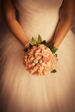 Wedding bouquet in bride's arms Stock Photography