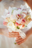Wedding bouquet in bride's hands with orchids anf roses Royalty Free Stock Image