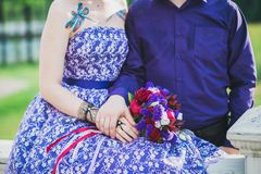Wedding bouquet in bride`s hands in purple dress near groom Royalty Free Stock Photo