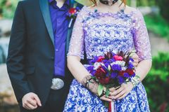 Wedding bouquet in bride`s hands in purple dress near groom Royalty Free Stock Photos