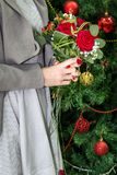 Wedding bouquet in bride`s hands. Wedding bouquet of red roses in bride`s hands, in front of christmas tree. Holiday and winter wedding concept. Close up Royalty Free Stock Images