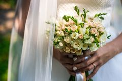 Wedding bouquet in bride`s hands. Vivid green bakground. Wedding elegant bouquet in bride`s hands. Vivid green bakground royalty free stock photos