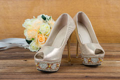 Wedding bouquet with bride's shoes on wood background Royalty Free Stock Photography