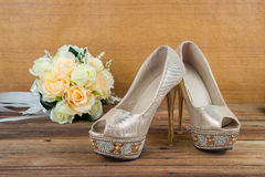 Wedding bouquet with bride's shoes on wood background Stock Photography