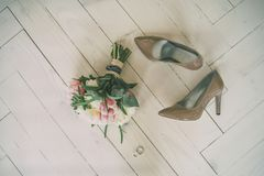 Wedding bouquet and bride`s shoes on the wooden floor 2. Wedding white pink bouquet and bride`s beige shoes on the wooden floor with rings Stock Image