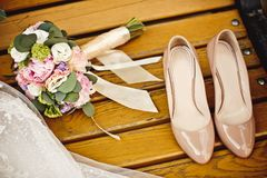 Wedding bouquet and bride shoes. Close up of wedding bouquet and bride shoes Stock Image