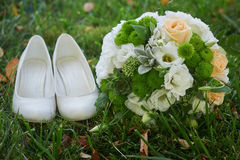 Wedding bouquet and the bride's white shoes on grass Stock Image