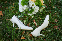 Wedding bouquet and the bride's white shoes on grass Stock Photo