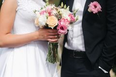 Wedding bouquet in brides hands. Close up view of couples hands holding wedding bouquet. Flowers royalty free stock photography
