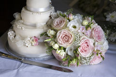 Wedding bouquet and cake. Wedding bouquet of pink and white roses alongside the cake Stock Photo