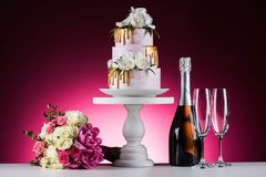 Wedding bouquet, cake and champagne. On pink royalty free stock photo