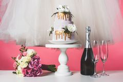 Wedding bouquet, cake and white dress. Isolated on pink stock photography