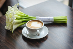 Wedding bouquet of calla lilies on a table with a cup of coffee Royalty Free Stock Photos