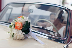 Wedding bouquet on car bonnet Royalty Free Stock Images