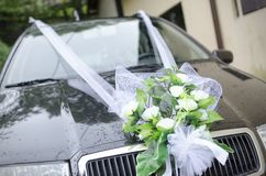 Wedding bouquet on a car. Decorative floral wedding bouquet on the front of a luxurious car royalty free stock photos