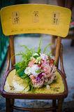 Wedding bouquet on chair. The groom in a suit or Bridesmaid is holding a wedding bouquet before church Stock Photos