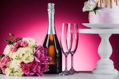 Wedding bouquet, champagne and cake on stand. On pink stock images
