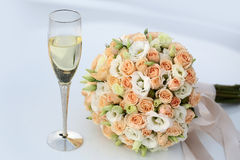 Wedding bouquet and champagne glass Stock Images