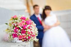 A wedding bouquet close-up against the background of the bride and groom on their wedding day stock photos