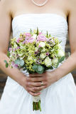 Wedding bouquet. Close up of a bride holding a wedding flower bouquet Stock Photos
