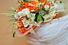 Wedding gown and bouquet. Close-up of a wedding gown and bouquet royalty free stock photography