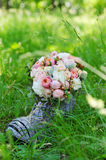 Wedding bouquet closeup. Wedding decoration details, closeup of flower bouquet in decorative wicker boot against green nature Stock Images
