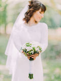 The wedding bouquet consisted of white daisies in the hands of the bride. The wedding bouquet consisted of white daisies in the hands of the bride Stock Photography