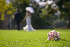 Wedding bouquet  & a couple. Beautiful wedding bouquet with the blurred couple on the background Stock Photos