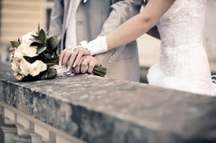 Wedding bouquet. Couple's hands holding wedding bouquet of flowers. Imitation of antiquity Stock Photos