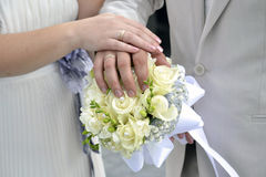 Wedding Bouquet. Couple's hands with rings on wedding bouquet Royalty Free Stock Image