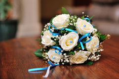 Wedding bouquet of cream roses and green leaves on wooden bench Royalty Free Stock Photography