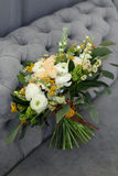 Wedding bouquet of cream roses and white peonies in a rustic style on a background of gray sofa. Bridal bouquet. The bride`s bouquet. Beautiful bouquet of white Royalty Free Stock Images