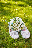 Wedding bouquet of daisies and white summer sandals Stock Photos