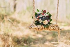 wedding bouquet of dark berries, roses outdoors on the decorated decorated village swing royalty free stock image