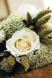 Wedding Bouquet Detail. Closeup of a wedding bouquet with a white rose and greens Stock Photo