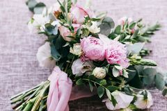 The wedding bouquet of fiancee of tender tints lies on fabric from flax. The wedding bouquet of fiancee of tender tints of flowers peonys, roses, chrysanthemums stock photography