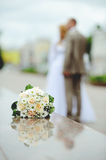 Wedding bouquet. Flowers against the groom and the bride Royalty Free Stock Photos