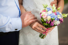 Wedding bouquet of flowers in hands of beautiful anonymous young Royalty Free Stock Photos