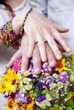 Wedding bouquet from  flowers and hands with rings Stock Images