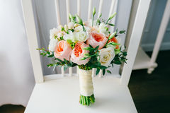 Wedding bouquet of flowers on the white wooden chair. Close-up. Indoors Royalty Free Stock Photography