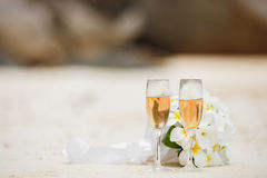 Wedding bouquet of frangipani and champagne glasses Royalty Free Stock Photos