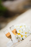Wedding bouquet of frangipani and champagne glasses Stock Photo