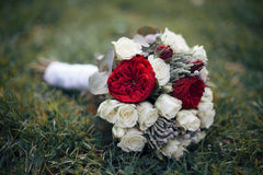 Wedding bouquet of freshly cut flowers, roses and peonies on grass closeup stock images