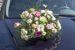 Wedding bouquet on the front cover of  car. Wedding bouquet on the front cover of a blue car Royalty Free Stock Photography