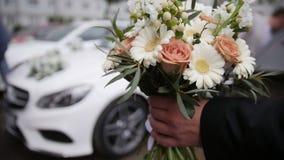 Wedding bouquet in front of luxury car