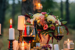 Wedding bouquet  with  glasses, vine,  candles and fruit outdoor Stock Images