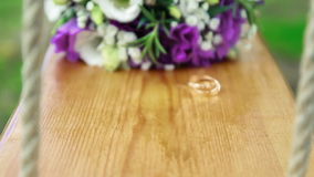 Wedding bouquet and golden rings on seesaw stock footage